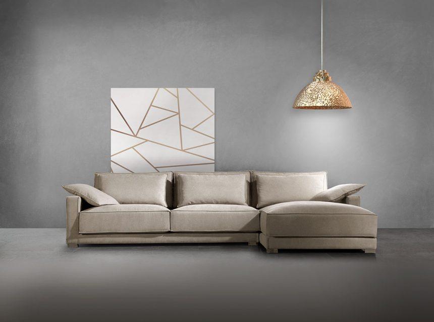 Vista frontal de sofá chaise longe tapizado en microfibra de color beige . Estancia de color gris medio. Con cuadro abstracto de grandes dimensiones de fondo blanco con líneas rectas y gruesas de color dorado. Además incluye lámpara de color dorado.