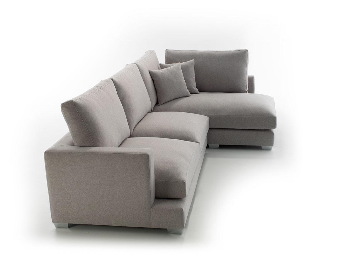 Vista lateral del modelo en fondo perdido blanco. Sofá chaiselonge tapizado en microfibra de color beige y patas metálicas