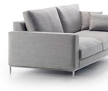Imagen en blanco y negro. Vista lateral del modelo a fondo perdido blanco. Se aprecia el lateral rectangular del asiento. La base inferior del sofá tiene una banda metálica que rodea todo el contorno del sofá, y se unen en torno a las cuatro patas que permiten la elevación de esa parte inferior.
