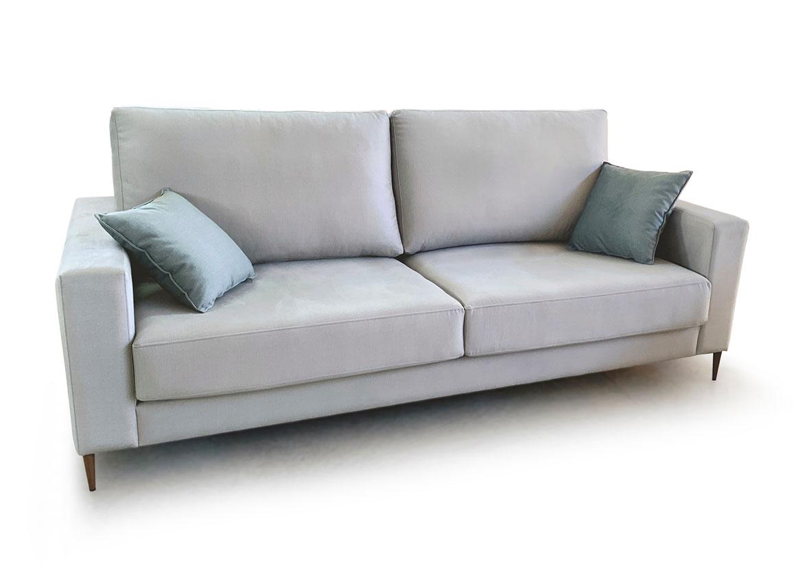 Vista semi-frontal del modelo a fondo perdido. Donde vemos su tapizado de microfibra en color celeste. Con cojines en azul marino. Brazos de tamaño reducido y patas de madera semicilíndricas que elevan la base del sofá.