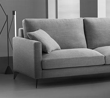 Detalle del brazo y asiento con cojin. Sofá tapizado en microfibra con brazo de ancho reducido. Imagen en blanco y negro.