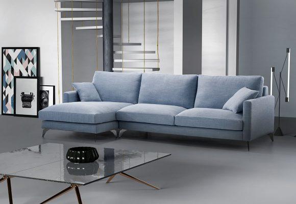 Sofá chaiselonge tapizado en microfibra en color azul. La estancia en tonos grises, incorpora una mesa rectangular con tapa de cristal y patas en metal. Marcos con fotografías retro apoyadas en la pared. Lámpara moderna de metal con dos focos rectangulares y unas escaleras de caracol.
