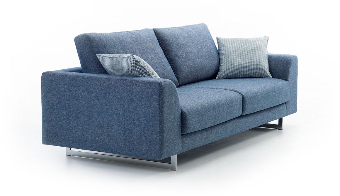 Sofá tapizado en microfibra de color azul saturado. La estancia incorpora una alfombra de color gris, dos mesas con tapa circular. Y una estantería con lejas en las que se apoya libros y una lámpara. La pared tiene un masillado que crea textura y es de color friío.