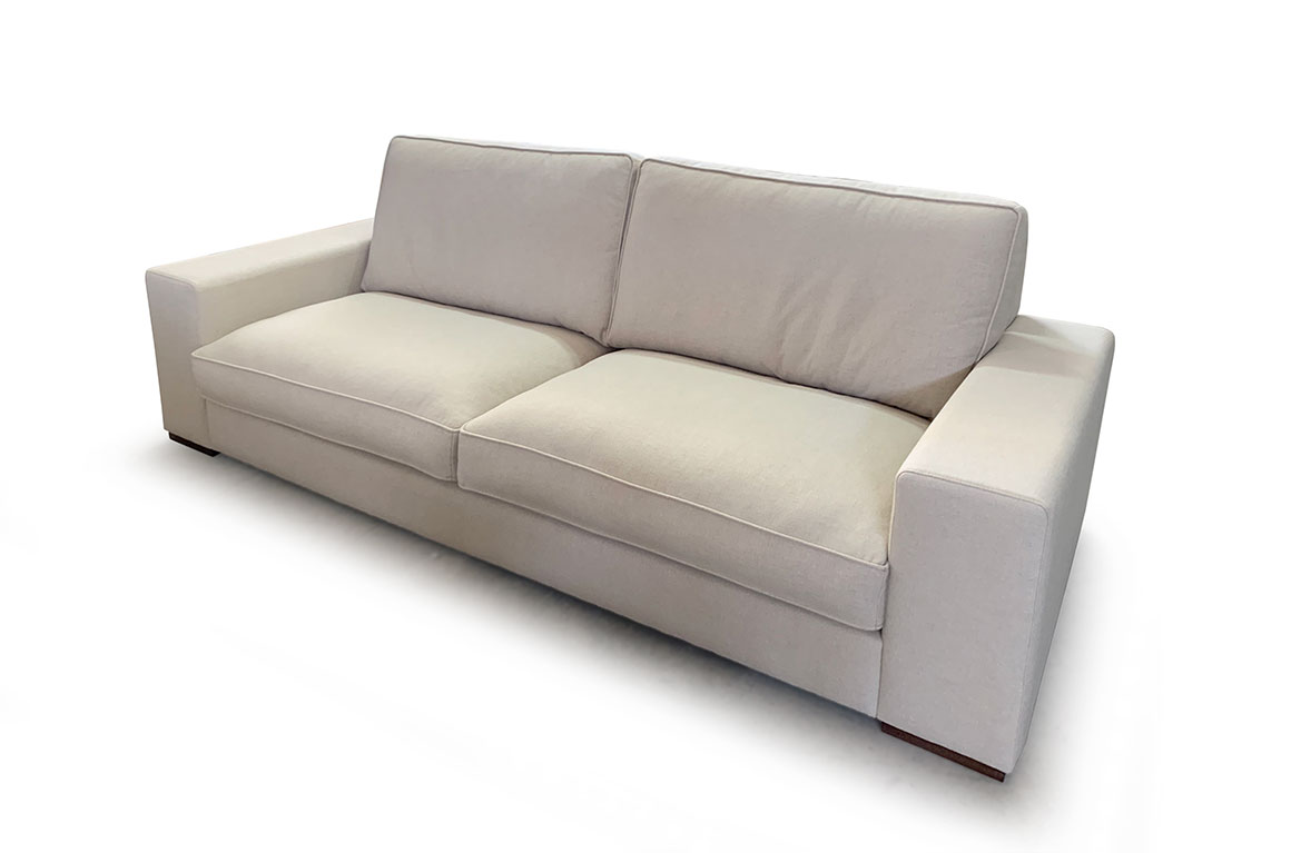 Vista tres cuartos del sofá a fondo perdido blanco. Brazos rectangulares con ancho medio o superior. Patas de madera en color negro. Modelo sin almohadas.