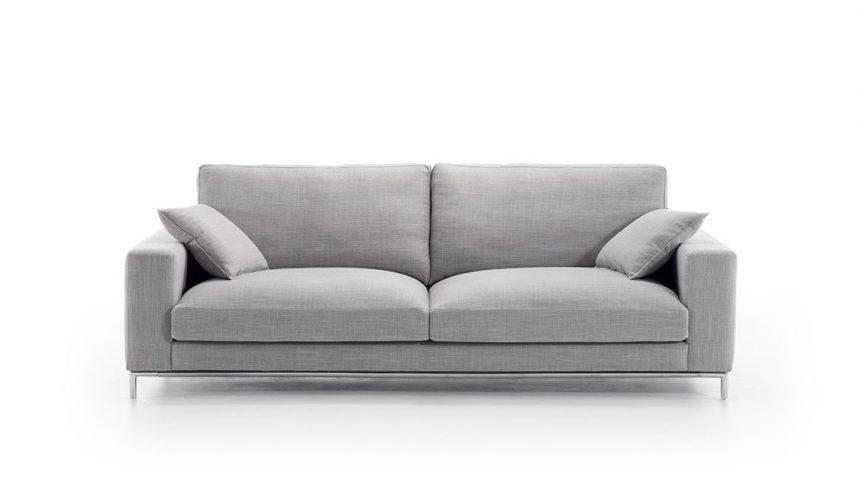 Vista frontal del modelo a fondo perdido de color blanco. Sofá tapizado en microfibra de color gris claro con patas metálicas. Incluye dos cojines de color similar al sofá.