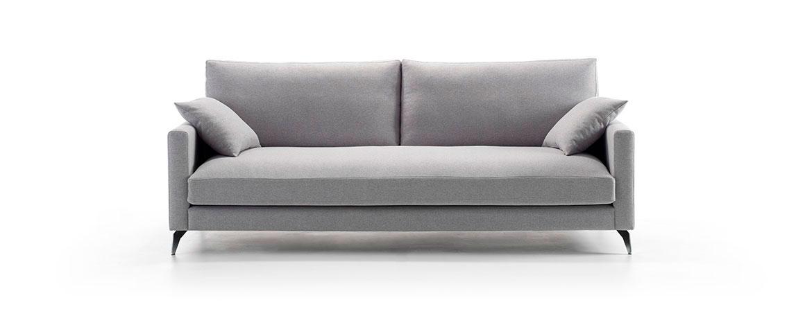 Vista frontal del modelo sobre fondo blanco. Sofá tapizado en microfibra de color gris metalizado. Incluye dos cojines de la misma tela, y patas metalizadas sin lacado. Brazos de ancho reducido.