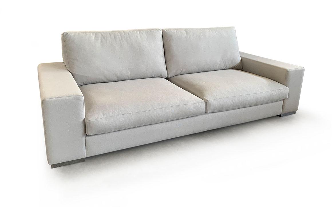 Vista semi frontal del modelo a fondo perdido. Sofá tapizado en microfibra de color hueso. Brazos rectangulares y patas metálicas.