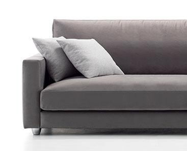 Vista frontal, modelo a fondo perdido detalle del sofá, donde vemos parte del asiento izquierdo con el brazo de mínimo anchura y dos cojines. Tapizado en microfibra de color gris oscuro con patas de metal redondeadas.