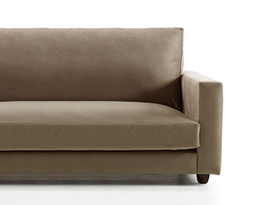 Vista frontal modelo a fondo perdido detalle del sofá donde vemos parte del asiento derecho y el brazo de mínima anchura. Patas de madera redondeadas. Tapizado en microfibra de color marrón tierra.