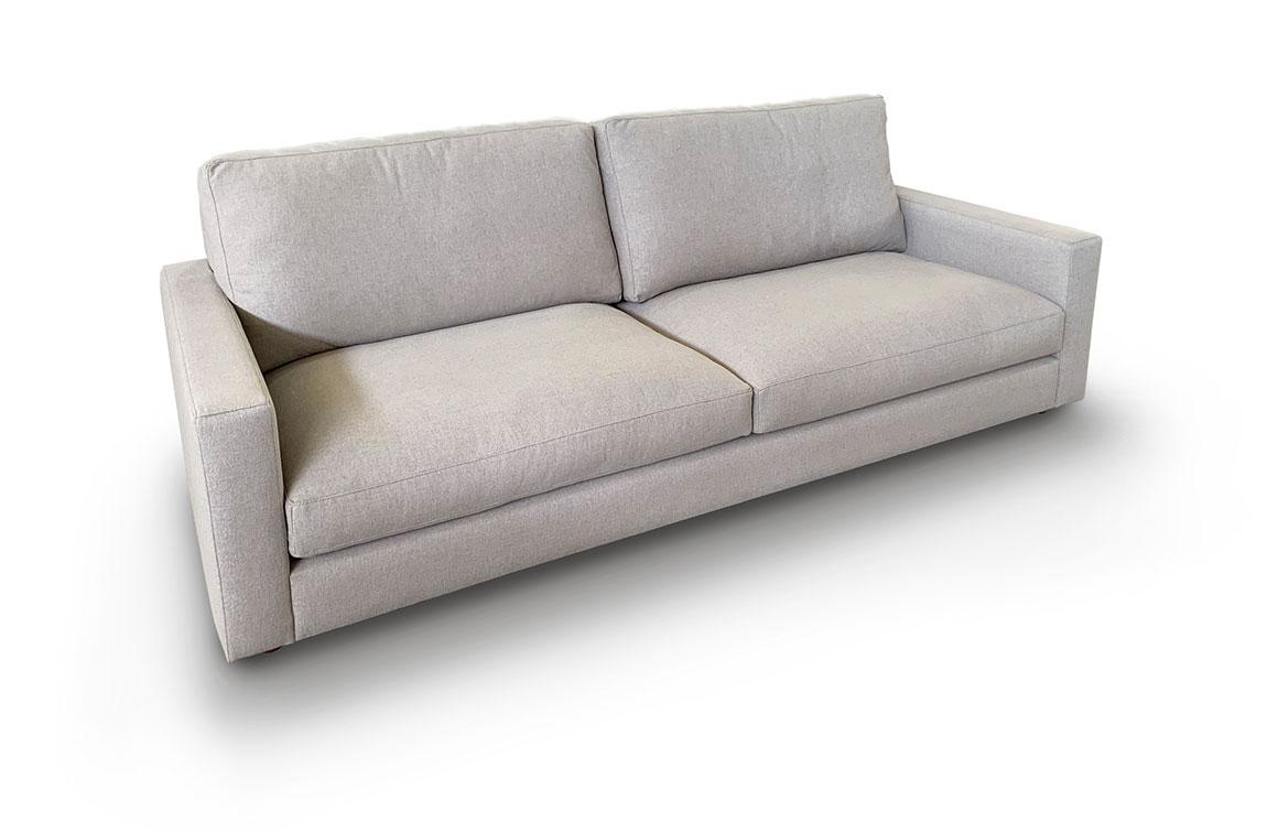 Vista tres cuartos del modelo a fondo perdido blanco. Brazos geométricos de mínima anchura. Sofá tapizado en microfibra de color beige claro.