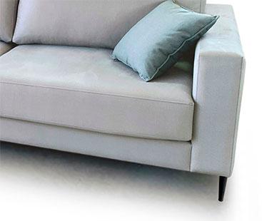 Modelo vista semi frontal a fondo perdido blanco. Tomamos un detalle de la zona derecha del sofá, donde se ve la parte inferior del asiento, un cojín y el brazo de ancho reducido.