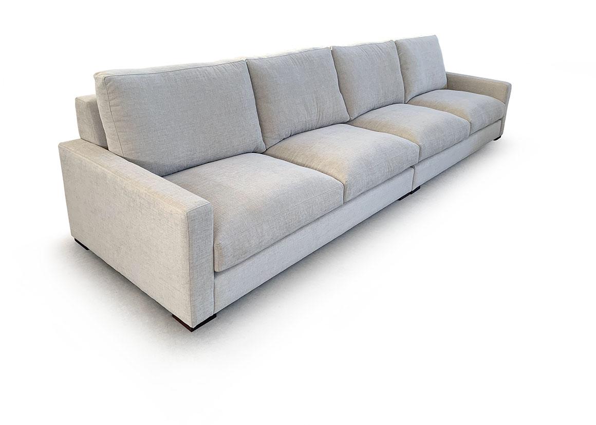 Vista del sofá en tres cuartos a fondo perdido blanco. En esta ocasión se ve el modelo completo con cuatro asientos sin cojines. Vemos el lateral izquierdo con brazo geométrico de ancho reducido.