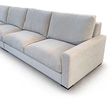 Vista del sofá en tres cuartos a fondo perdido blanco. Donde se ha reducido el encuadre soló vemos el lado derecho. Que contiene dos asientos con brazo geométrico rectángular y brazo de mínima anchura.
