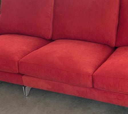 Detalle del asiento sofá tapizado en microfibra color rojo. Patas metalizadas sin lacado.